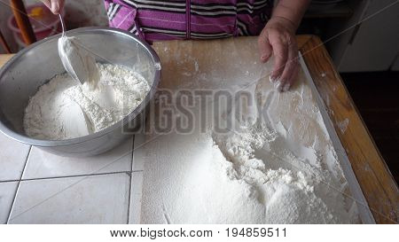 Adding flour to the base for the dough in a metal bowl. Kneading dough.
