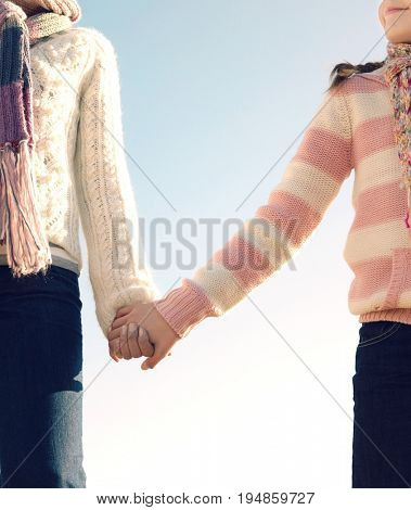 Low angle view of cropped mother and daughter holding hands against clear sky
