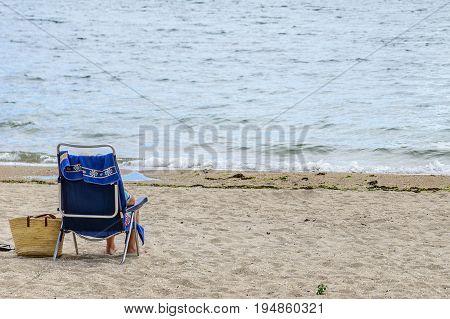 man in the beach deck chairs on the beach, rear view