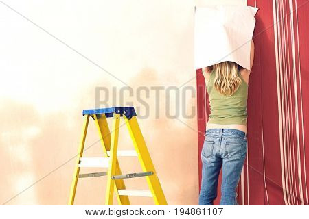 Rear view of a blond young woman hanging wallpaper