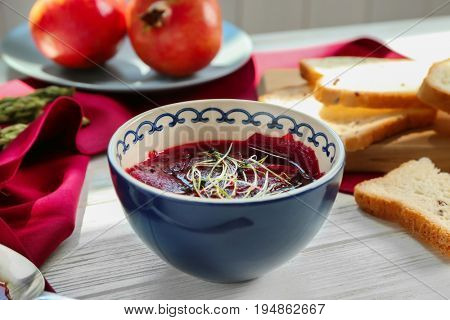 Delicious beet soup with wheat germs in bowl on kitchen table