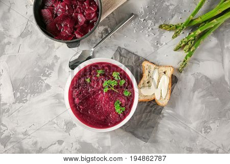 Delicious beet soup with parsley leaves on kitchen table