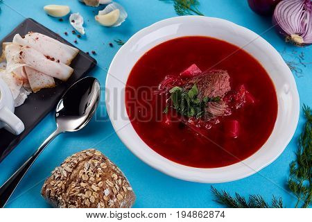 ukrainian soup borsch on blue color background. Traditional ukrainian dish borsch isolated on white table. first course