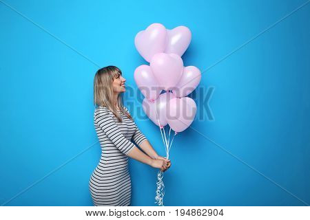 Portrait Of Young Woman With Pink Heart Balloons On Blue Background