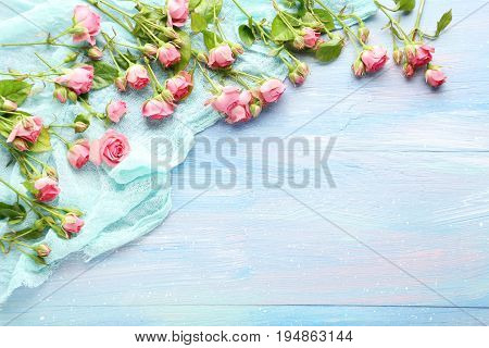Pink Roses With Gauze Fabric On The Blue Wooden Table