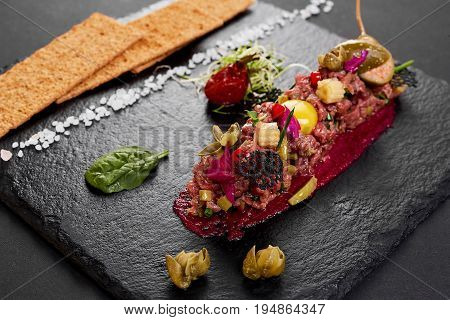 fresh beef tartar with salt and herbs and Crispbread, studio shot. Meat tartar on black shale.