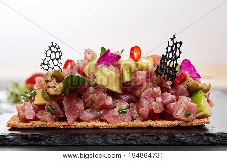 fresh tuna tartar with salt and herbs, studio shot. Fish tartar on black shale