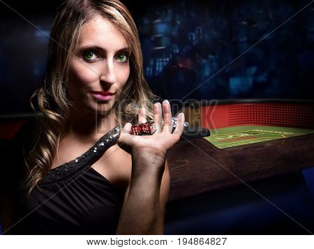 sensual woman before dice throw on craps table at casino