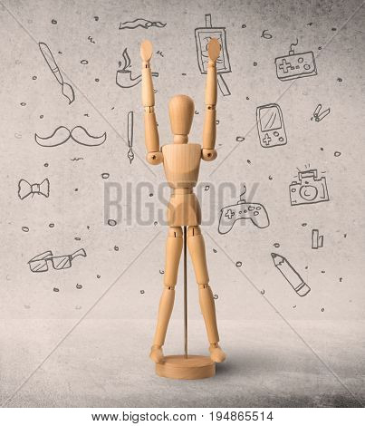 Wooden mannequin posed in front of a greyish background with hobby related scribbles behind it