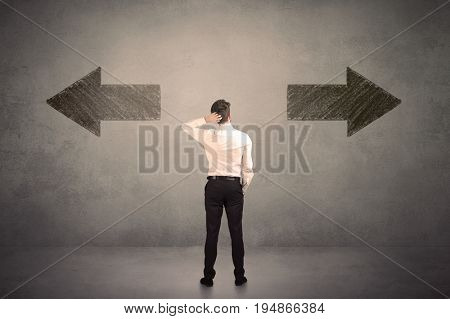 Business man taking a decision while standing in front of two grungy arrows on wall concept