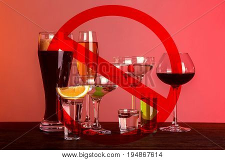 Different alcohol drinks in glasses with STOP sign on red background