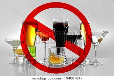 Different alcohol drinks in glasses with STOP sign on grey background
