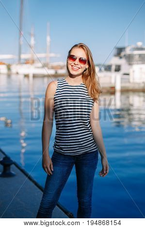Portrait of white Caucasian blonde woman with tanned skin striped t-shirt and blue jeans by seashore lakeshore with yachts boats on background on water lifestyle summer hobby leisure concept