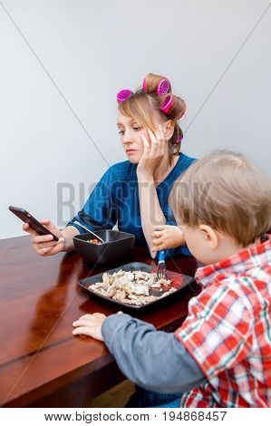 Bored tired white Caucasian young woman mother housewife with hair-curlers in hair looking on phone surfing Internet. Child son boy sitting eating meal lunch. Lifestyle concept.