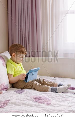 Portrait of cute adorable white Caucasian toddler boy sitting in bed playing with digital tablet with funny face expression. Candid lifestyle early development. New technology generation.