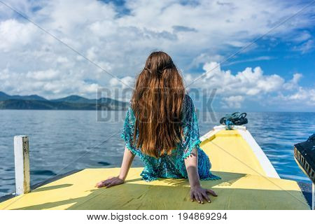 Rear view of a young woman sitting on a jetty in a relaxing day of summer during vacation in Flores Island, Indonesia