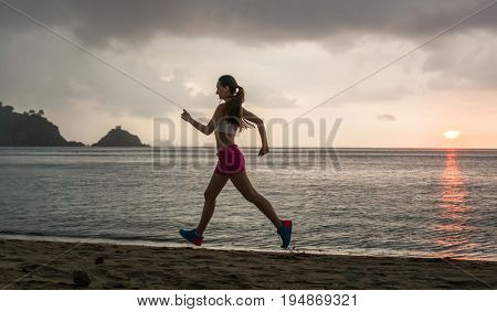 Fit young woman with a healthy lifestyle smiling while running on the beach during summer vacation in a cloudy day in Flores Island