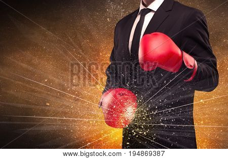 A successful powerful business person in red boxing gloves concept with illustrated power lines and pieces falling apart in front of explosion.