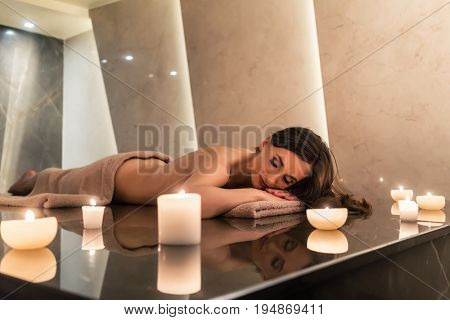Scented round candle  next to young woman on marble massage table during aromatherapy at luxury spa and wellness center