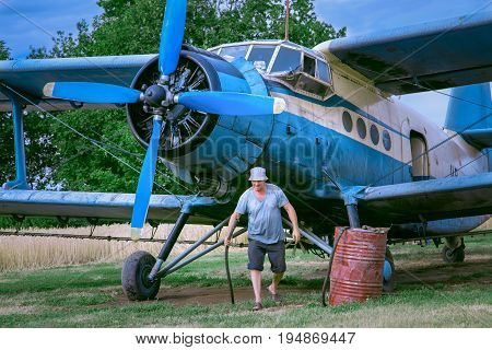 Mid adult man is fueling an airplane	Man is holding a hose in right hand. A gas barrel is standing nearby the biplane.