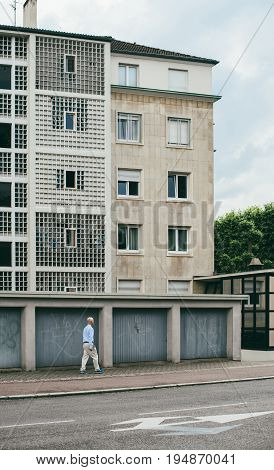 STRASBOURG FRANCE - MAY 30 2017 Bald man walking near the garage doors with social building Banlieue in the background