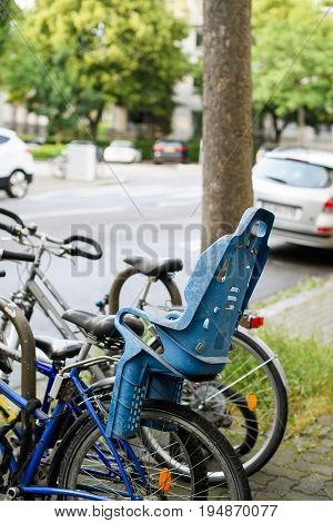Modern bicycle with blue security confort kid child seat behind in city environemnt
