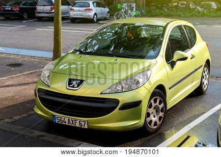 STRASBOURG FRANCE - MAY 30 2017: Lion logotype of in front of a green Peugeot 206 city car parked on the street. Peugeot is one of the bigest car manufacturer in the world