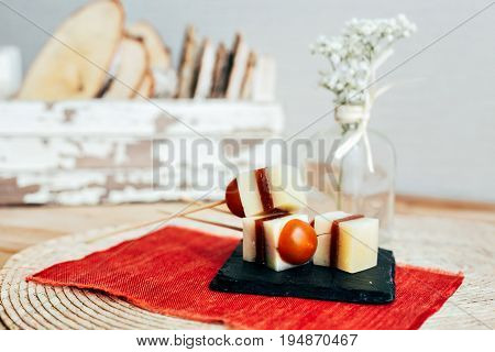 Still life of tapas appetizers sticks with cherry tomatoes spanish jamon or ham and cheese served for little party snack