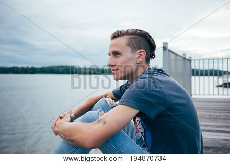 Handsome attractive man sits on deck or dock during sunset waits on boat to come fashionable and trendy short sides haircut