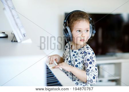 Beautiful little kid girl playing piano with headphones in living room or music school. Preschool child having fun with learning to play music instrument. Education, skills concept.