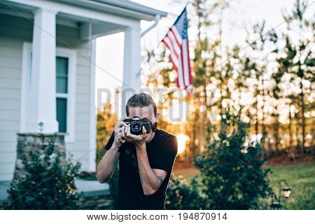 Teenage hipster millennial photographer with analog vintage retro camera makes photo on porch or driveway of his house with american patriotic flag