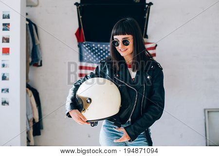 Hard rock brunette beautiful woman with round glasses and motorcycle black leather jacket and white retro vintage helmet stands in front of american flag in cool apartment