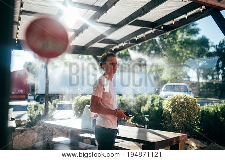 Attractive millennial man with fashionable haircut in trendy outfit stands in line for brunch outside restaurant on terrace with sprinkled water for cooling on hot day