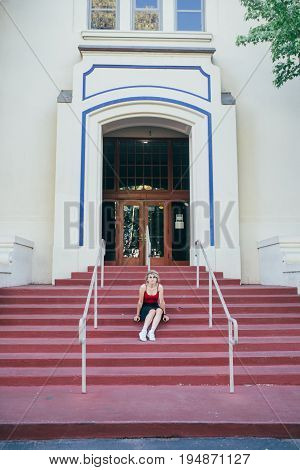 Young cute pretty teenager sits on steps to beautiful architecture building of highschool in average american town wears black skirt and round sunglasses sexy and fashionable