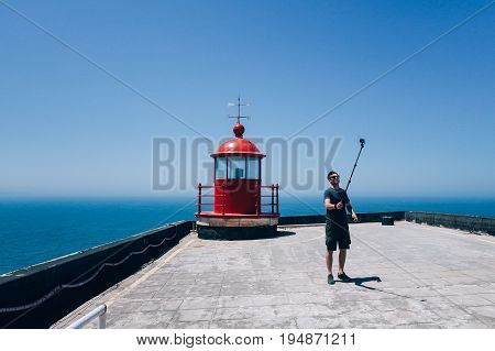 Handsome young man in traveler outfit stands near bright red lighthouse sets up timer on smartphone on selfie stick ready to make photo for social media