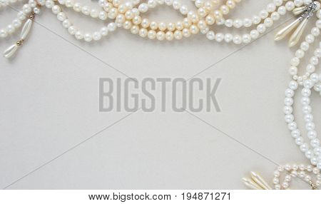 Woman's Jewellery. Frame with old vintage pearl beads pearl earrings. Beautiful vintage jewelry on grey. Flat lay top view