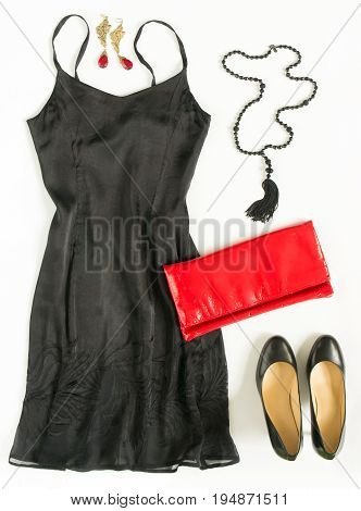Cocktail dress outfit night out look on white background. Little black dress red evening clutch black shoes black tassel necklace. Flat lay top view