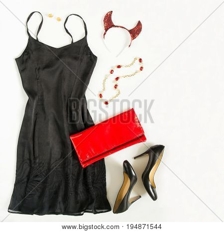 Christmas party outfi. Cocktail dress outfit night out look on white background. Little black dress red evening clutch black shoes red ang gold necklace and devil horns. Flat lay top view