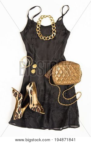 Christmas party outfit. Cocktail dress outfit night out look on white background. Little black dress gold bag leopard shoes gold necklace. Flat lay top view