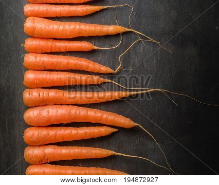 Carrots Of Various Sizes Lined Up In A Row On A Black Wooden Background. Washed And Ready To Eat.