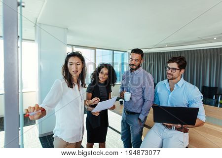 Business investors discussing a point in boardroom. Business woman pointing towards the board while making a business presentation at office.