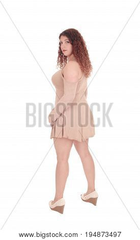 A beautiful Caucasian woman standing in a beige dress from the back looking over her shoulder isolated for white background.