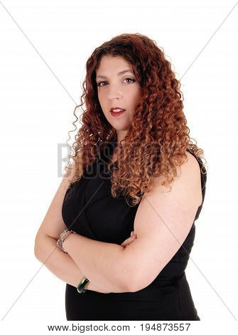 A young business woman stand in in a black dress with her arms crossed looking into the camera isolated for white background.