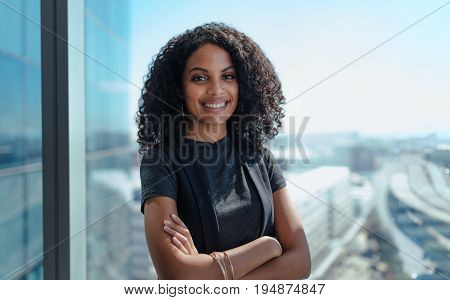 Closeup of a smiling businesswoman standing by the window of her office. Young woman with curly hair and arms crossed standing in office.