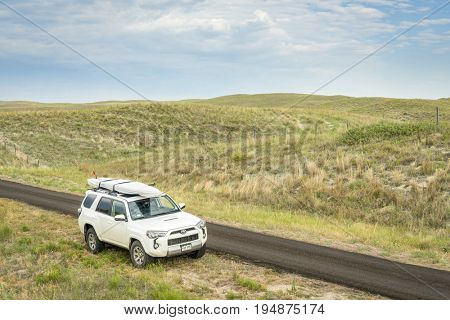 SENECA, NE, JULY 7, 2017: Toyota 4Runner SUV (2016 Trail edition) carrying  a stand up paddleboard on a narrow back country road in Nebraska Sandhills