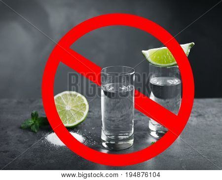 Alcohol drink in glass with STOP sign on grey background