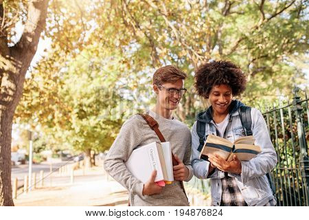 University students reading book in the college campus. Young college students with books on the street.