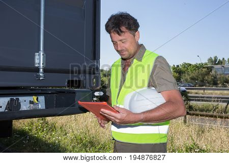 Foreman Or Working Man Hold Tablet Control Loading Containers Box To Trucks