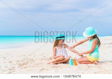 Sister applying sun cream to sister nose on the beach
