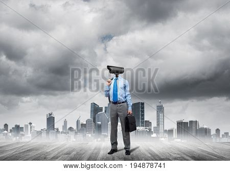 Elegant businessman outdoors with jacket on shoulder and camera instead of head